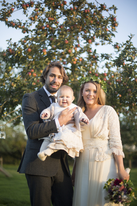 newlyweds holding their baby at their somerset wedding