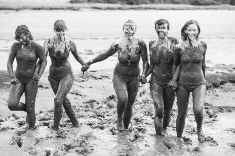 blak white group photo young girls walking thorough river mud together laughing
