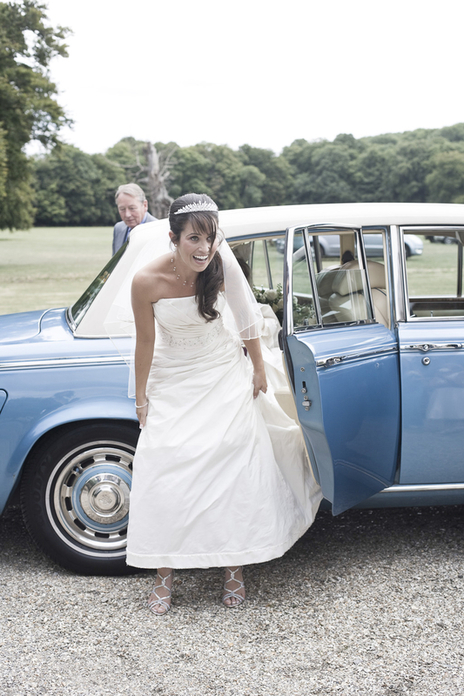 Gorgeous south west bride stepping out from a blue classic car with a huge smile