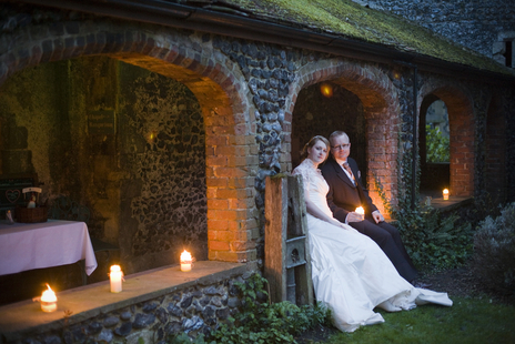 bride and groom sit by candlelight photo