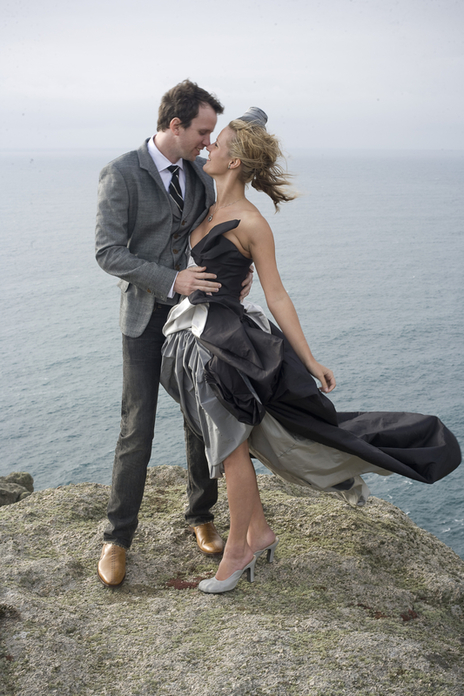 Stunning windswept clifftop wedding photo of Bride and Groom in each others arms on Lundy Island