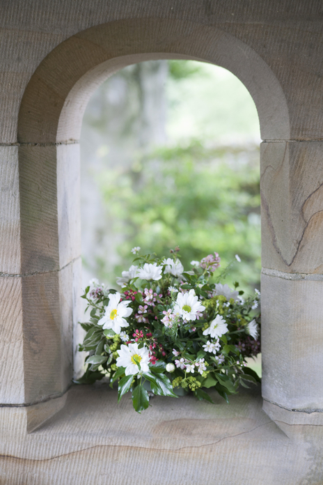 photo of wedding flowers resting in church window