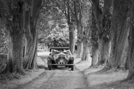classic car drives down church in wedding photography somerset