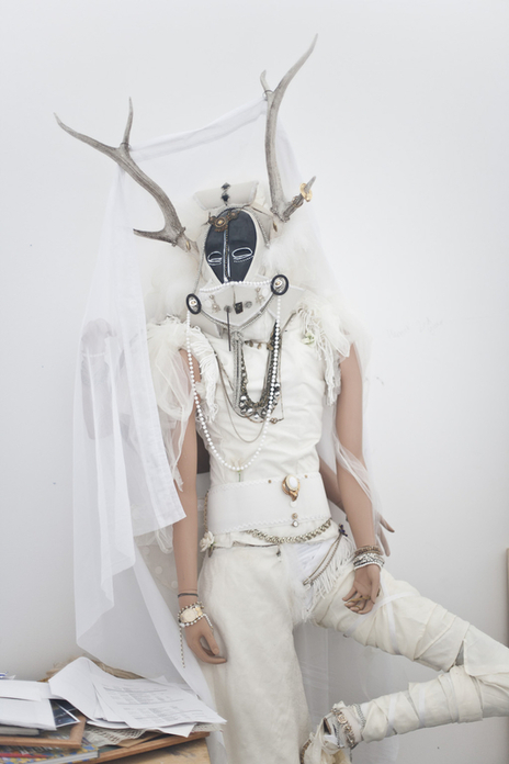 art work of mannequin and stag head dressed in white photo