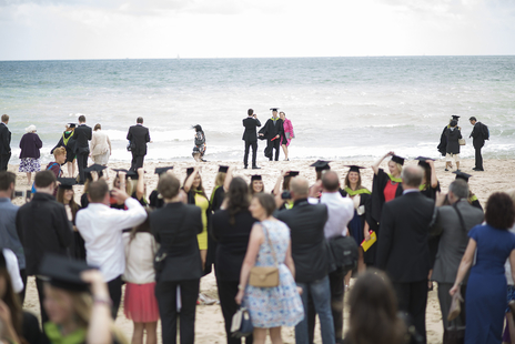a busy beach graduation scene, bournemouth
