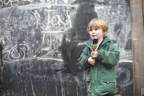 young school child holding a brush in from of blackboard