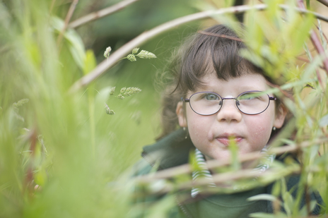 photo of a Somerset child peeking through grass at camera