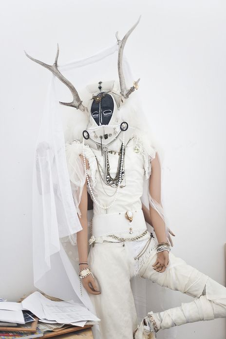 Art installation of a mannequin dressed in white with antlers