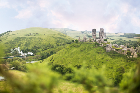 Photograph of Corfe Castle landscape with a steam train alongside it