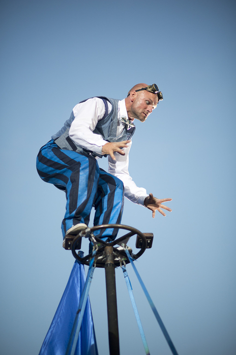 a manic looking actor atop a structure in the sky looking down