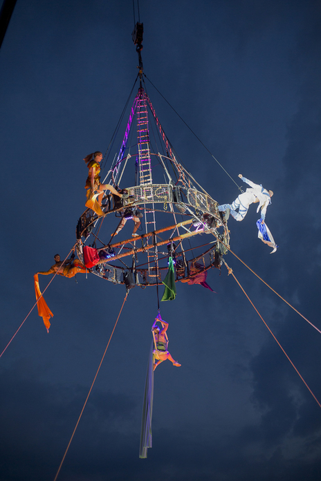 actors at night during a performance hanging from a structure in the sky