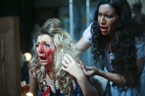 actresses in a play, one covered in blood looking at herself in the mirror