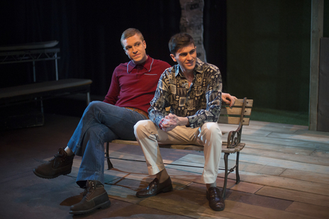 two actors sit on a bench in a play