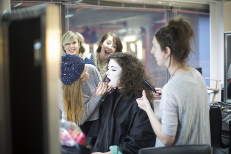 actress having make up applied backstage with others looking on