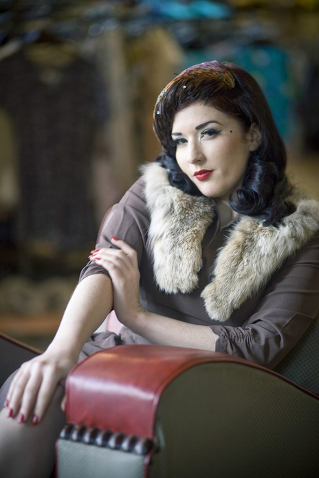 beautiful Burlesque performer poses in a chair and fur coat for photographer