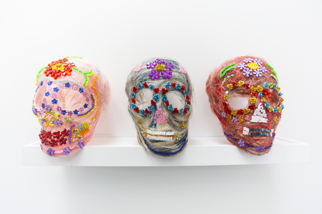 Three bright, multicoloured skulls as an art piece