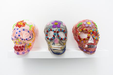 Three bright, multicoloured skulls as an art piece