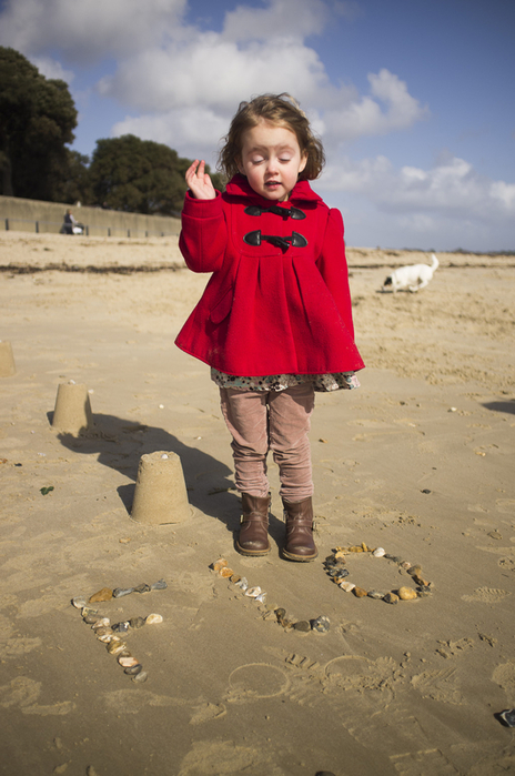 Photo of young girl in a red dress waving with eyes shut on the beach