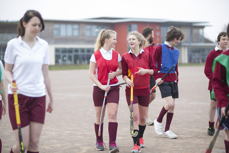two school girls in sports gear talk and walk together