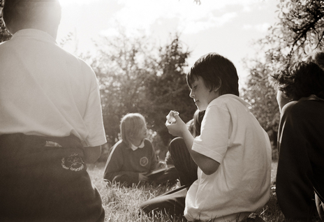 boy having eaten an apple thinks about it in the orchard photo