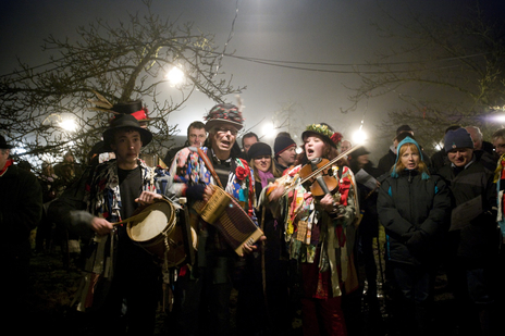 Photo of Morris Men singing at night in a Somerset cider portray celebrating Wassail