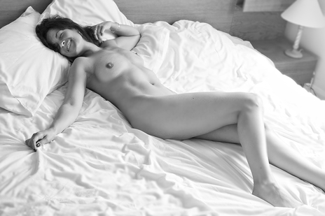 black and white photo of a nude woman on a bed laughing