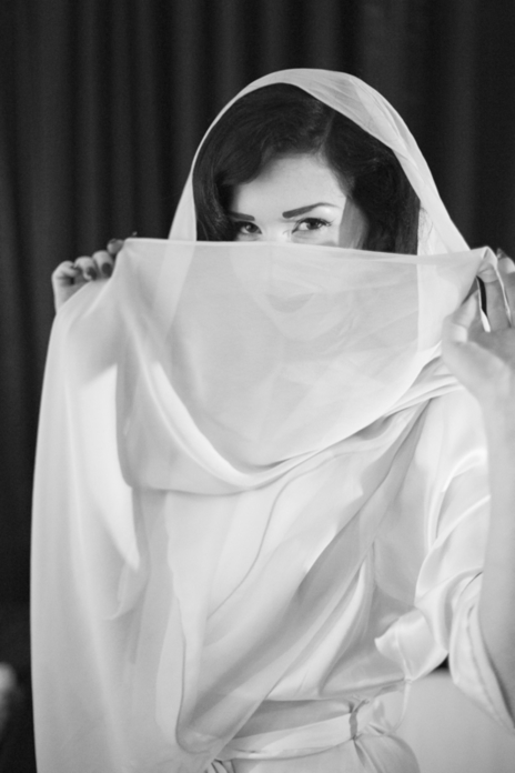 black and white missy fatale hiding face behind sheet