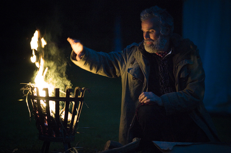 man by fire at a nighttime festival celebration  photograph