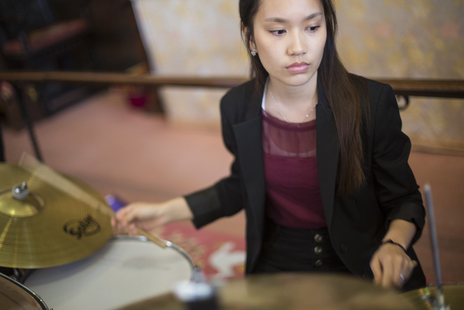 young asian lady plays the drums
