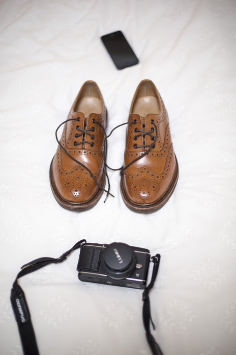 Wedding still life detail of brogues on a bed with a camera in the foreground