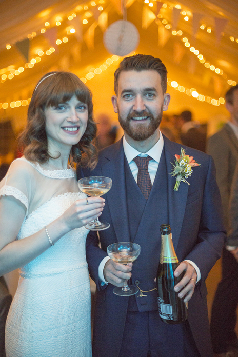 Cool looking bride and groom on smiling to camera at their wedding reception
