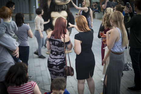 two women from behind chat at a ceremony