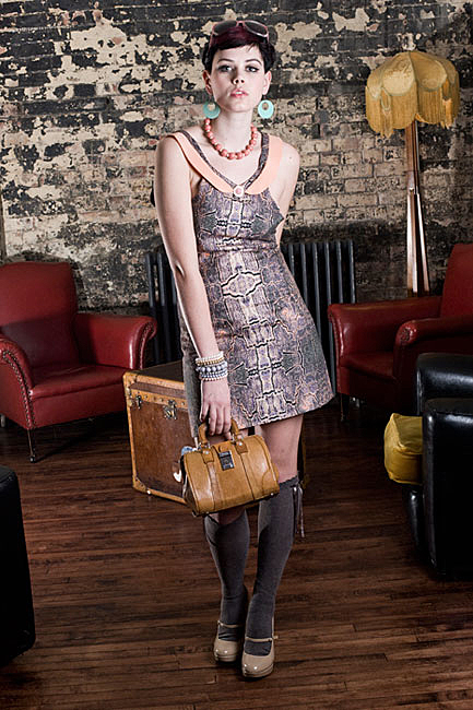 a fashion photo of a young female model in Somerset holding a bag