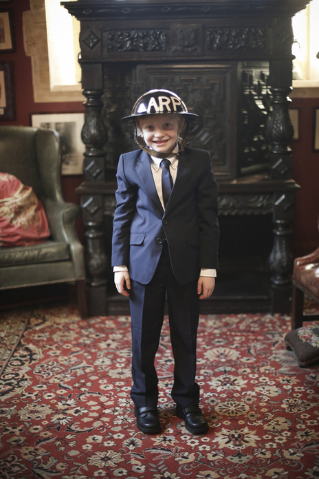 Young lad in a suit and wearing a WW2 air raid helmet smiling at a Dorset wedding