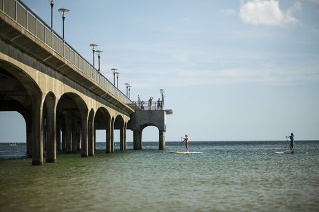 Photo of two women standing on paddle boards next to a sunny Bournemouth pier, Dorset
