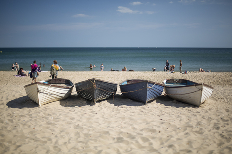 boats sitting on beach photo tourism dorset