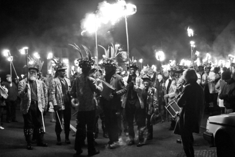 Groups of morris men process through the streets at night with fire