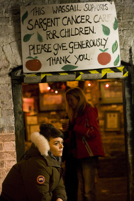 lone woman sites beneath a sign at a wassail photo