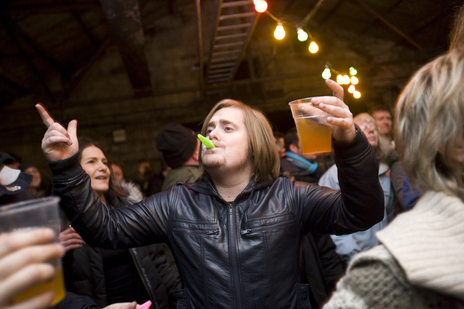 raver at a wassail blowing a kazoo holding cider photo