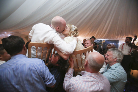 bride and groom on chairs kissing at their wedding reception
