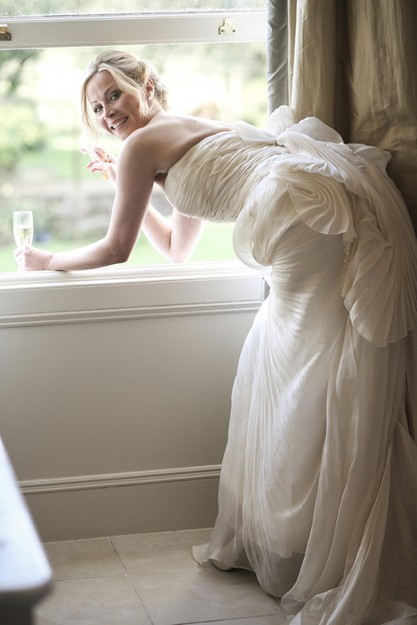 bride leans out of window in Somerset for a photo