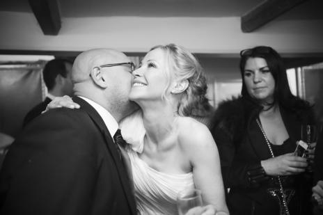 bride being kissed at wedding reception