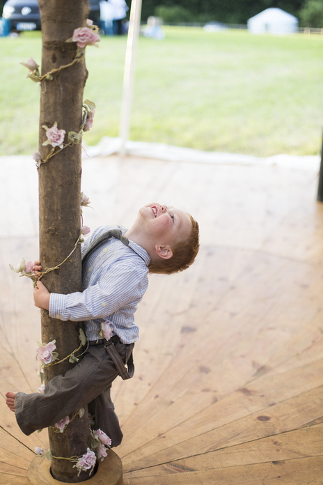 elated child grasping the marquee pole with his leg at a rural countryside wedding Devon, UK