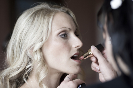 photo of bride having her lips painted on her wedding day