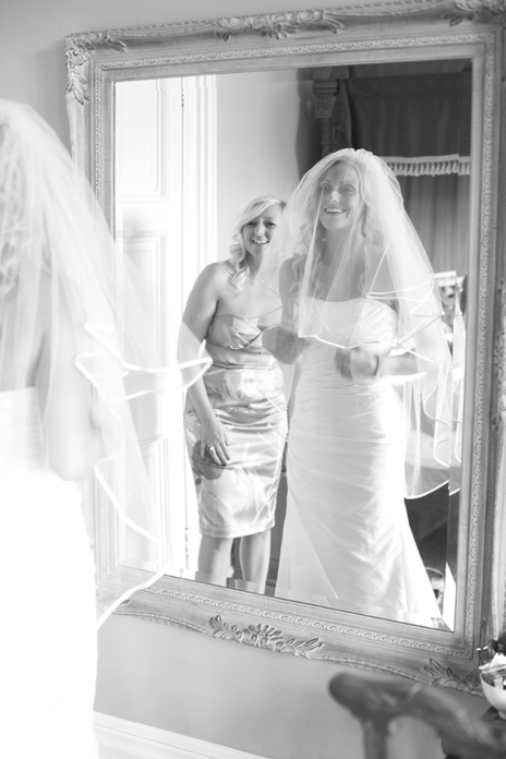 bride and bridesmaid looking in mirror smiling