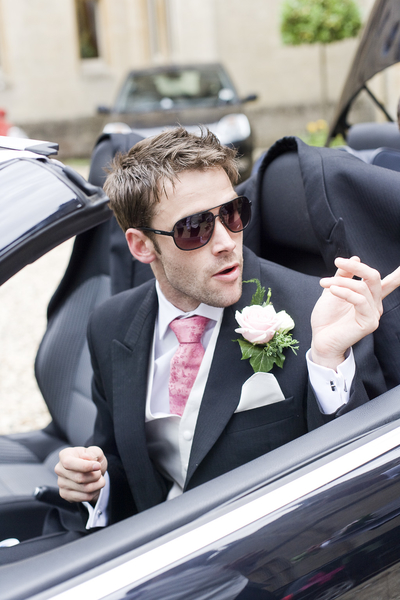 Groom in car wearing sunglasses at wedding photo