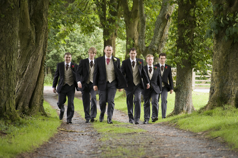 groomsmen walk up the road to the church photo