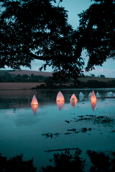 Beautiful evening landscape photo of lanterns floating gently down the river, Devon and Cornwall, UK