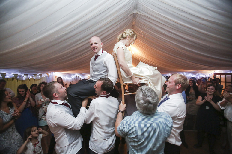 bride and groom are hoisted onto chairs for wedding photographer in Somerset