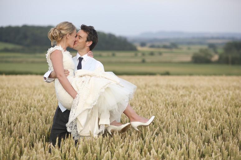 happy wedding couple kiss in a cornfield